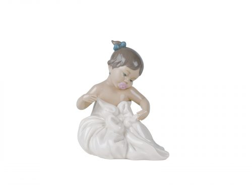 An adorable glazed porcelain figurine of a young girl with her lovely dark hair tied up into two buns, holding and looking at her favourite blanky. A memory I am sure a few of us can share. Size: 16 x 13 cm By Nao Product Code: 02001337
